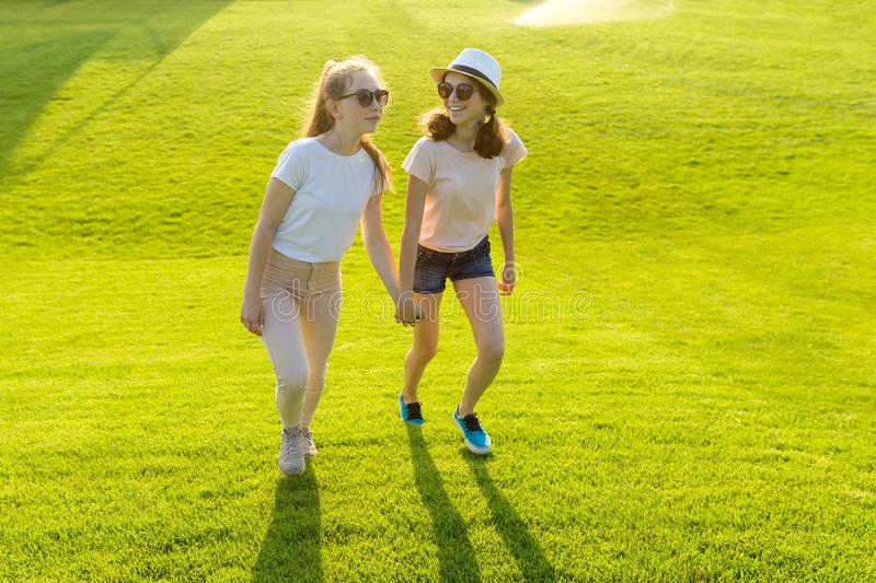 Two teen girls hold hands on the green grass in the park on a hot summer day at the golden hour. Friendship between teens stock images