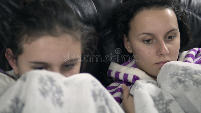 girls in pijamas sitting on the couch with blanket and watch horror TV royalty free stock photos