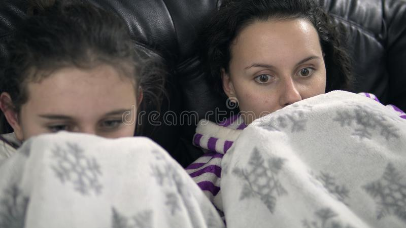 Two teen girls in pijamas sitting on the couch with blanket royalty free stock images