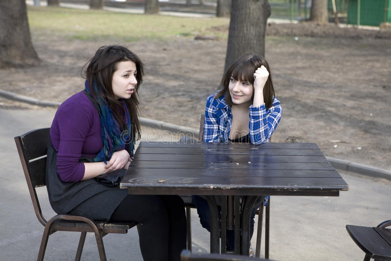 Two teen girls sitting in street cafe royalty free stock photography