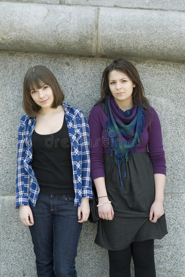 Two teen girls standing at wall stock image