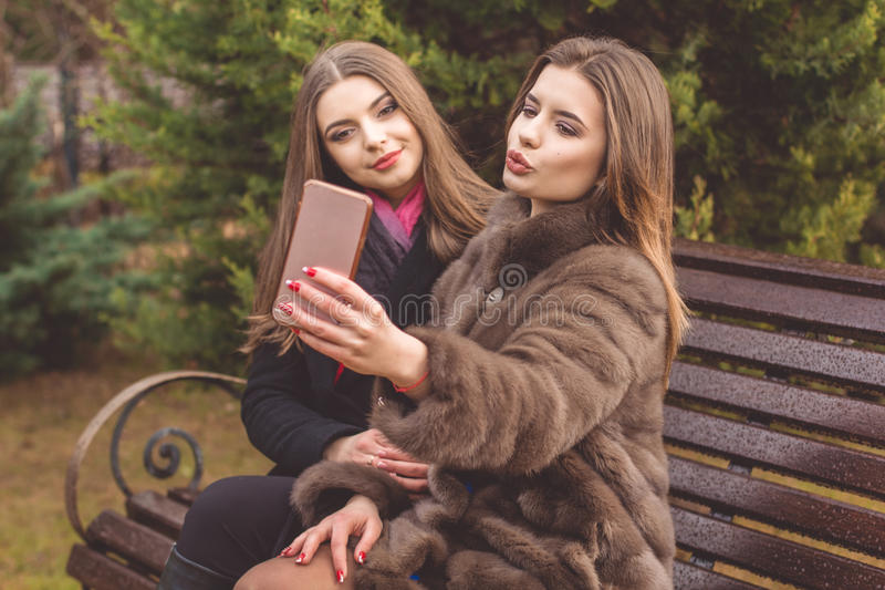 Two teen girls are taking selfie with smartphone. Two beautiful happy friends girls are wearing warm winter coats posing and taking selfie with smartphone stock photo