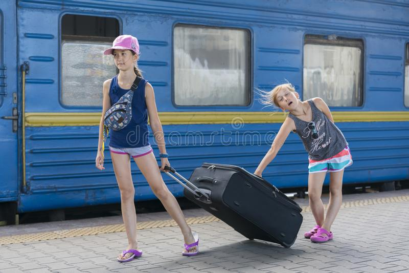 Two teen girls at the train station with a suitcase. Two sisters are pulling a large and heavy black suitcase against the. Background of the train stock photos