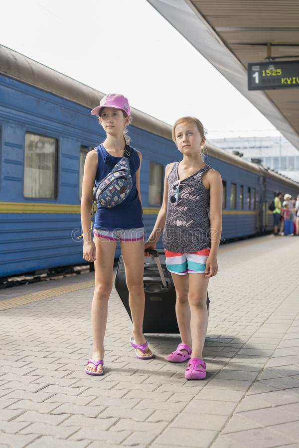 Two teen girls at the train station with a suitcase. Two sisters are pulling a large and heavy black suitcase against the stock image