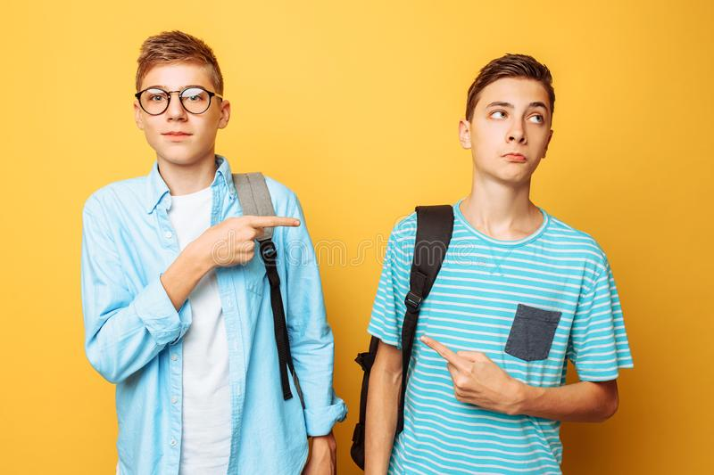 Two teen guys point at each other with their thumbs, blame and do not want to admit their guilt, isolated on a yellow background royalty free stock photo