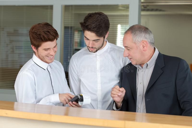 Two teen men and their teacher during their receptionist training. Receptionists royalty free stock image