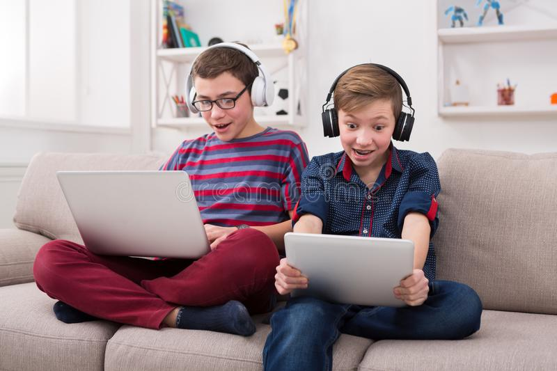 Two teenage boys with gadgets and headphones on couch at home royalty free stock images