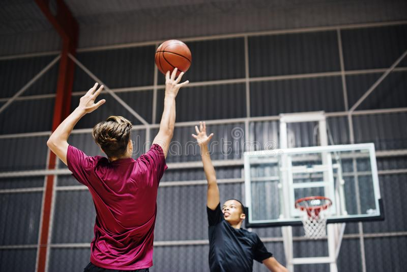 Two teenage boys playing basketball together on the court royalty free stock images