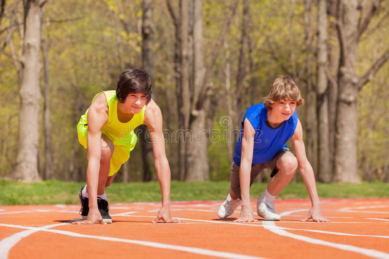Two teenage boys ready to start running on a track. Two teenage boys ready to start running and racing each other on the track in spring park royalty free stock photography