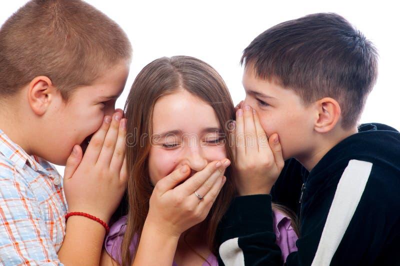 Two teenage boys telling jokes to teenage girl. Isolated on white royalty free stock images