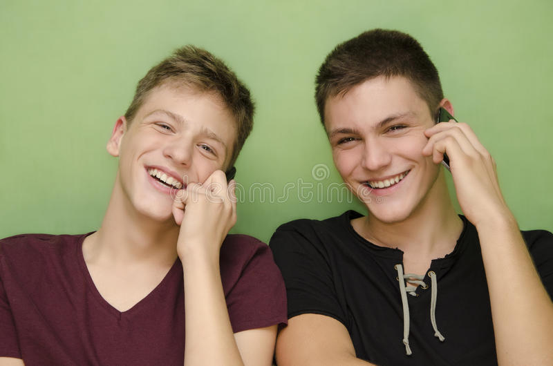 Two teenage brothers talking on smart phone. Two teenager brothers using smartphones and smiling, green background stock photos