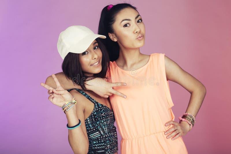 Two teenage friends in studio stock photo
