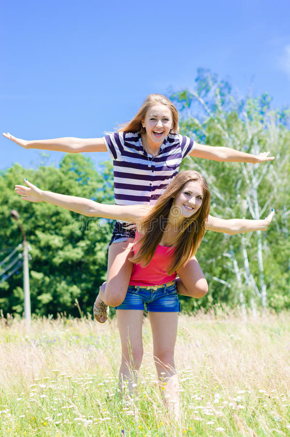 Two teenage girl friends having fun outdoors on summer day stock photos