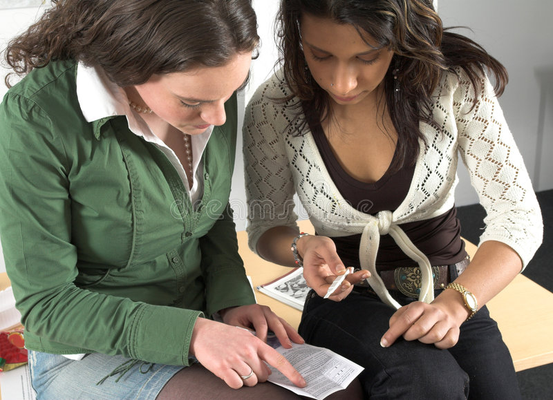 Two teenage girls checking pregnancy test royalty free stock images