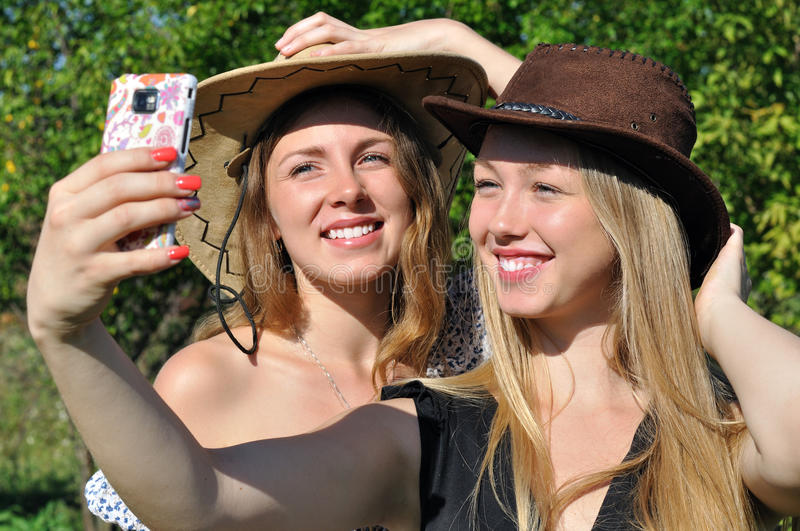 Two teenage girls in cowboy hats taking selfie stock photos