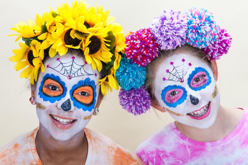 Two Teenage Girls in Dia de los Muertos Halloween Make Up. Two happy teenage teen girls in Dia de los Muertos Halloween make up stock photography