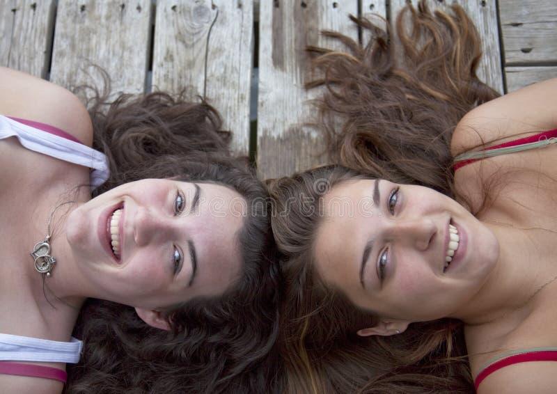Two Teenage Girls on Dock, Head to Head royalty free stock photography