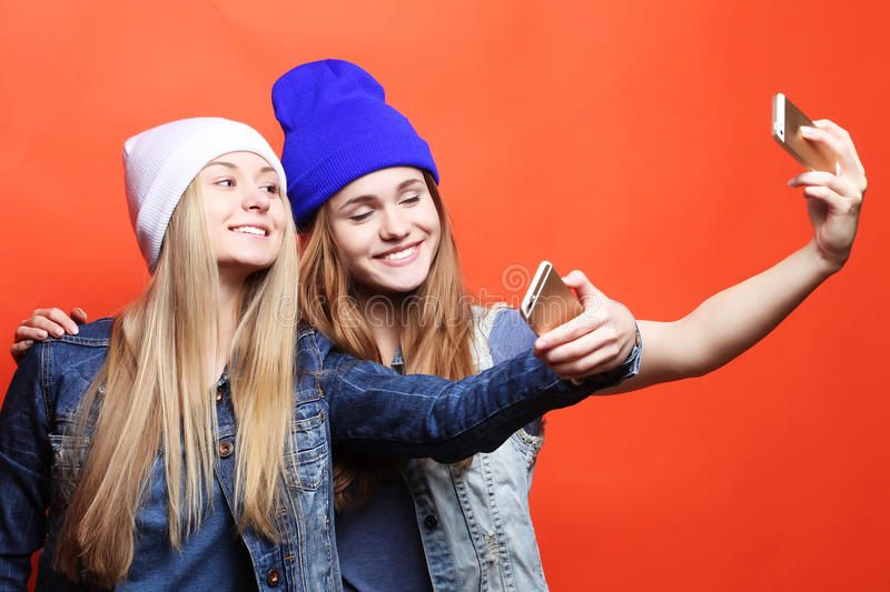 Two teenage girls friends in hipster outfit make selfie on a pho stock image