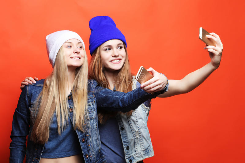 Two teenage girls friends in hipster outfit make selfie on a pho stock photos