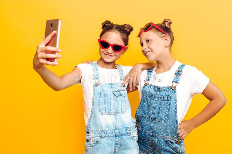 Two teenage girls, girlfriends have a rest and take a selfie on a smartphone on a yellow background royalty free stock photography