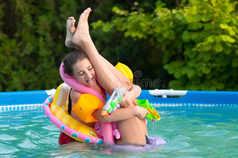 Two teenage girls having fun in the pool royalty free stock photography