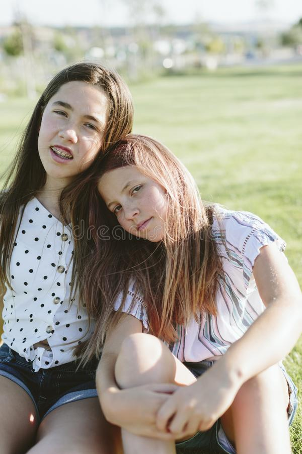 Two young girls sitting on the grass looking at the camera. Two teenage girls with heads together. They`re sitting on the grass. They have long hair. They`re stock photos
