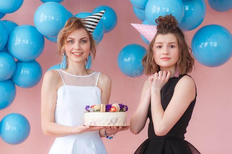 Two teenage girls holding birthday cake. Wearing black and white dresses and hats.  stock photos