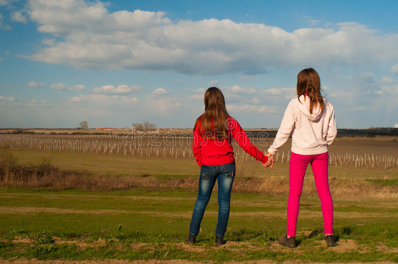 Two teenage girls holding hands in the nature stock images