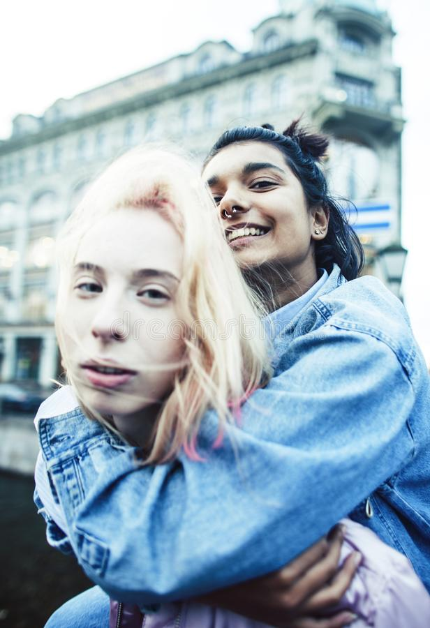 Two teenage girls infront of university building smiling, having fun, lifestyle real people concept close up. Two teenage girls infront of university building stock image
