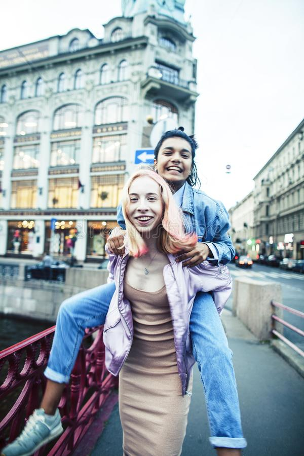 Two teenage girls infront of university building smiling, having fun, lifestyle real people concept close up stock photo