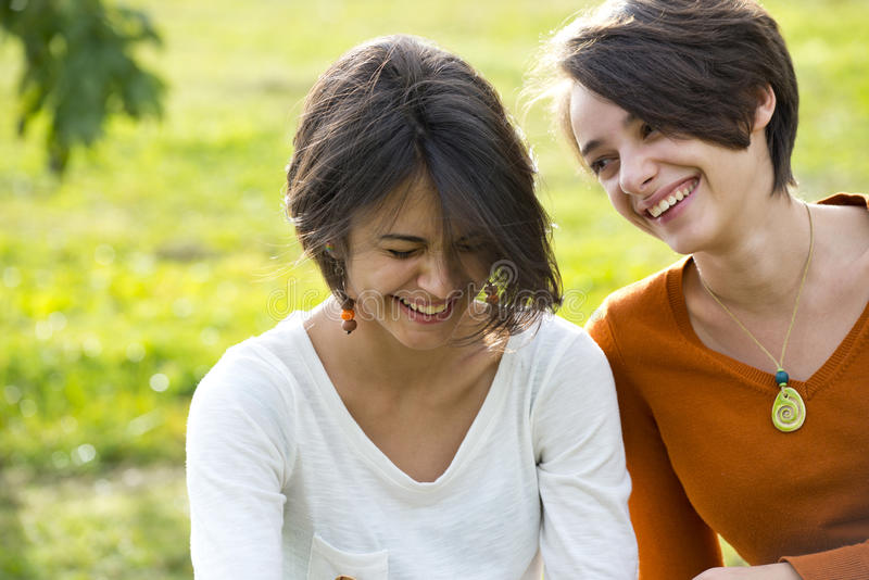 Two teenage girls laughting hard in park royalty free stock photos