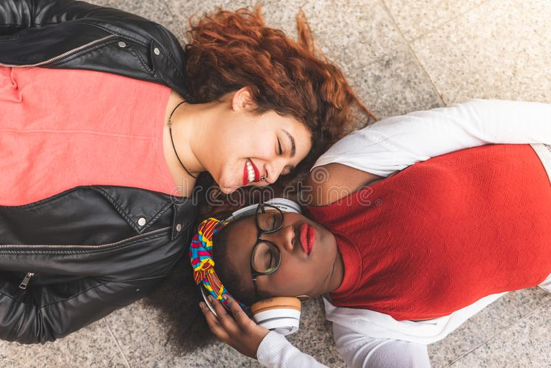 Two Teenage Girls Laying Down and Looking Each Other on The Floor stock photography