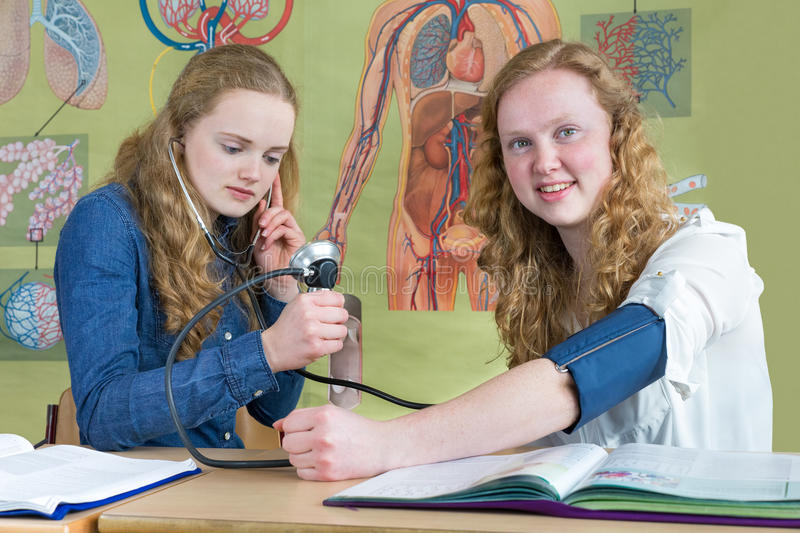 Two teenage girls measuring blood pressure in biology lesson stock photography