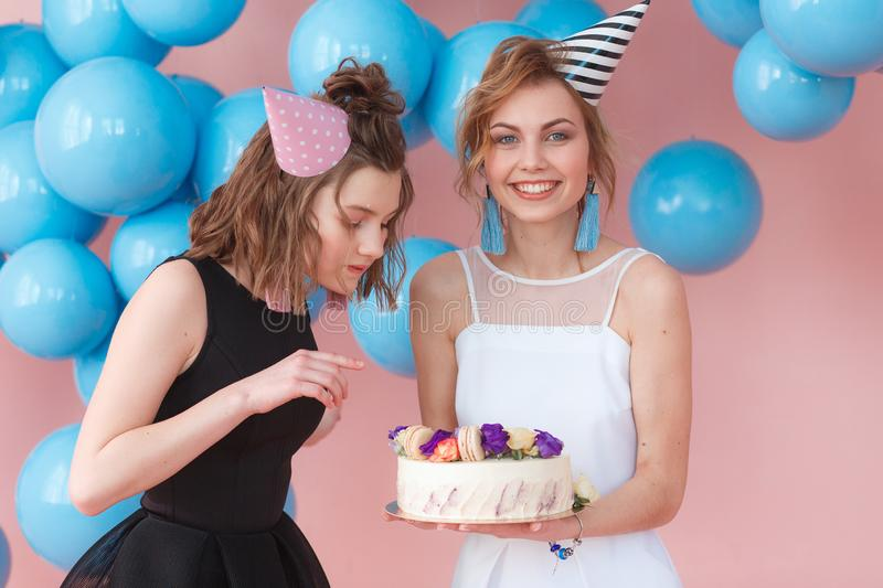 Two teenage girls in party hat holding cake. Isolated on pink background and blue balloons stock photos