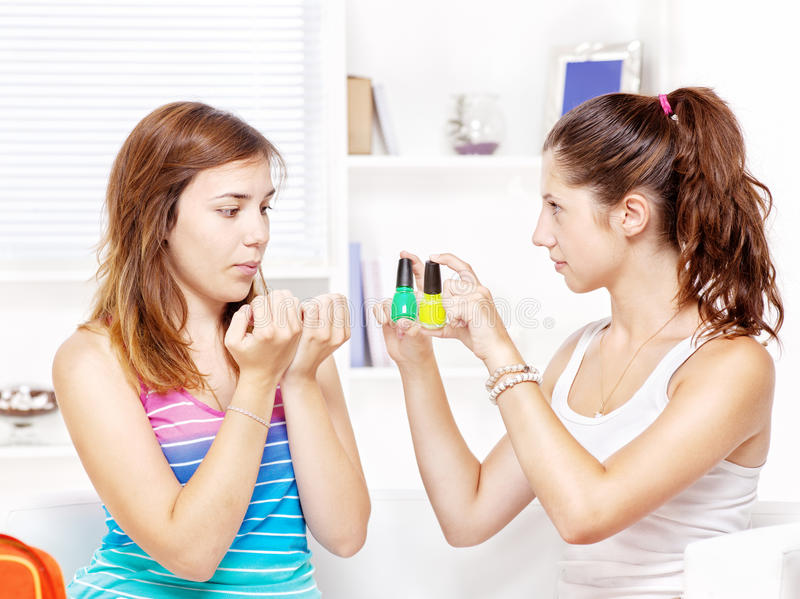 Two teenage girls polishing fingernails