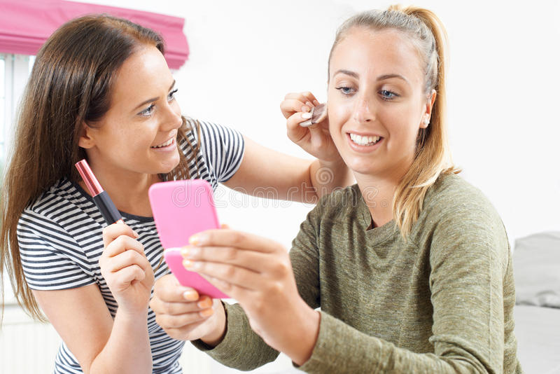 Two Teenage Girls Putting On Make Up In Bedroom stock photos