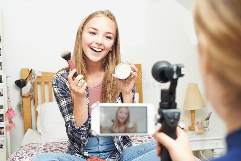 Two Teenage Girls Recording Beauty Blog In Bedroom royalty free stock image