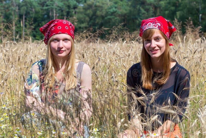 Two teenage girls sitting in corn field stock photos