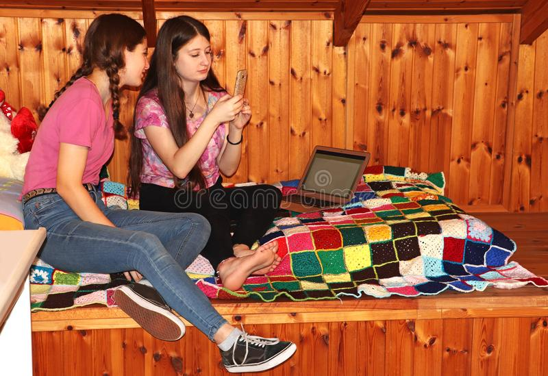 Two teenage girls sitting on the bed looking at the mobile phone royalty free stock photography