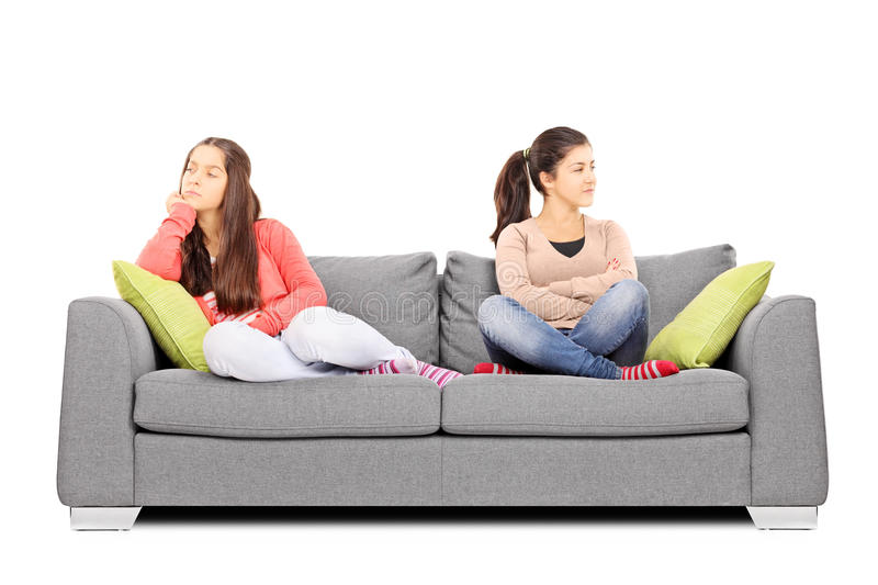 Two teenage girls sitting on sofa angry with each other. On white background stock image