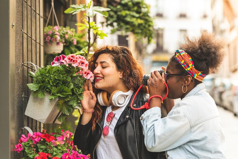 Two Teenage Girls Smelling Flowers stock photos