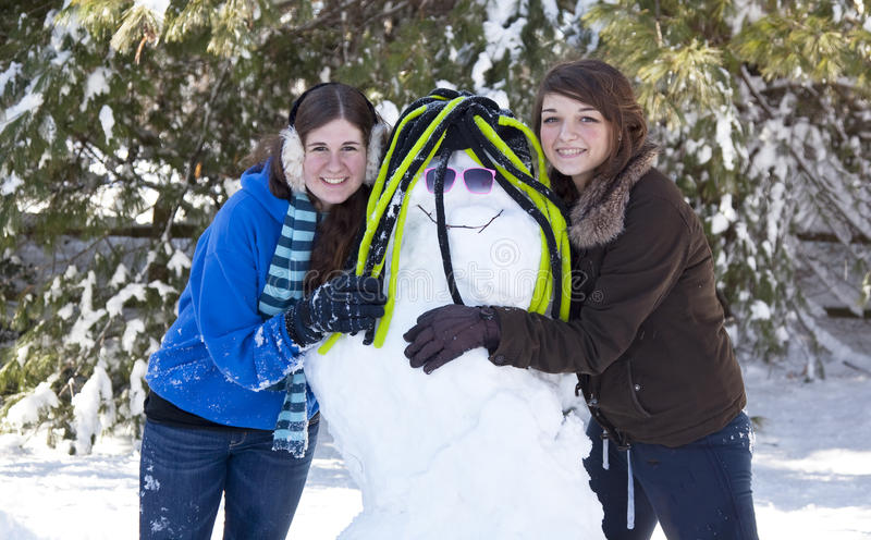 Two teenage girls with snowman stock photography