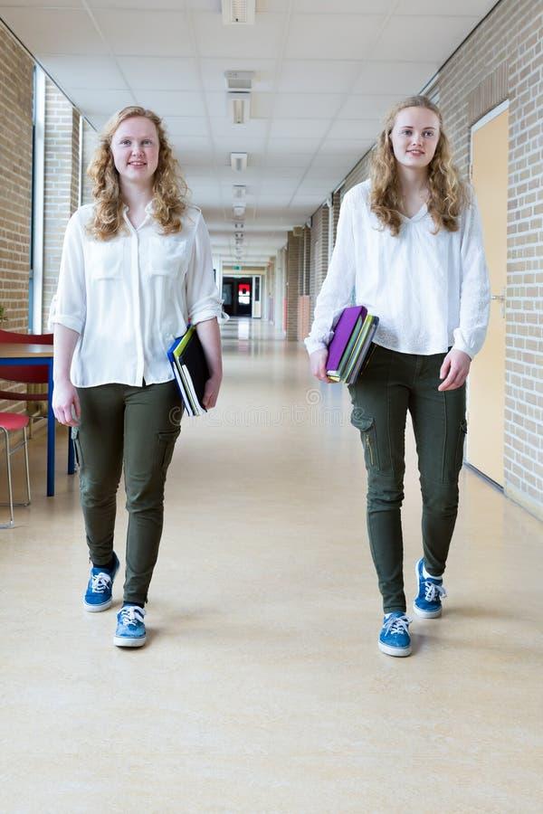 Two teenage girls walking in long school corridor carrying text books stock image