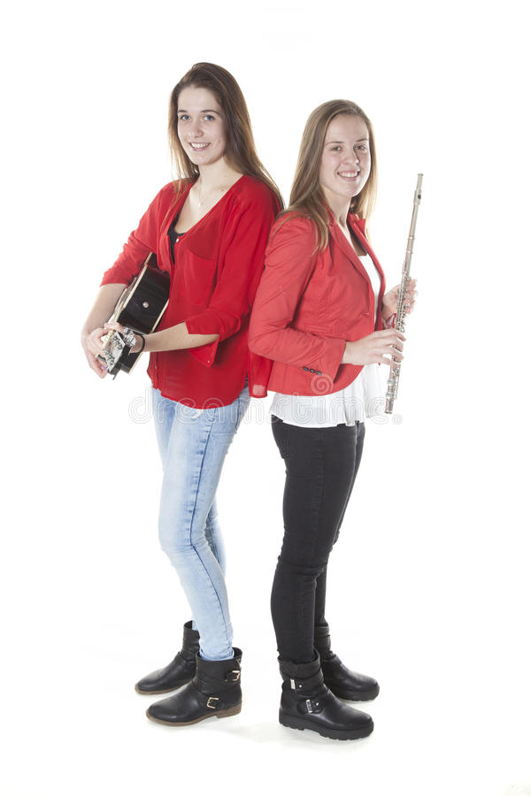 Two teenage sisters play flute and guitar in studio stock photo