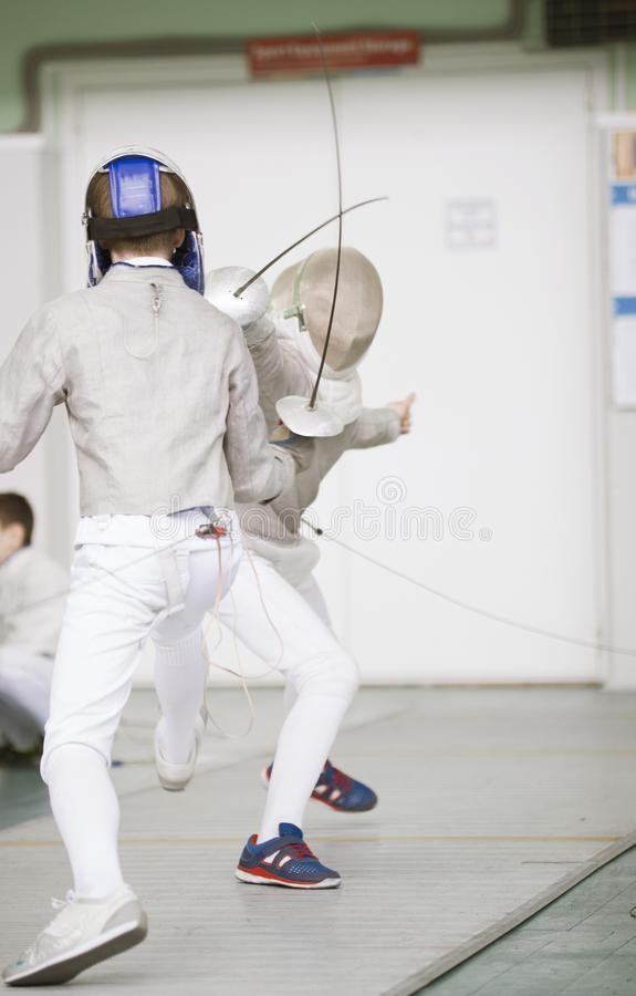 Two teenager fencers fighting with rapiers on the fencing tournament stock photos