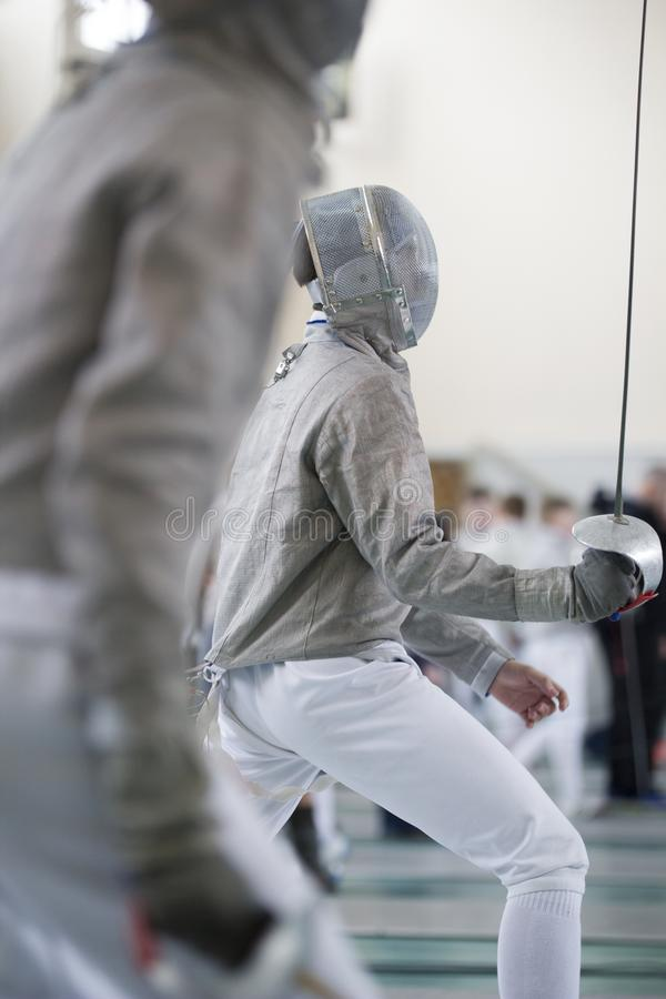 Two teenager fencers fighting with rapiers on the fencing tournament royalty free stock photos