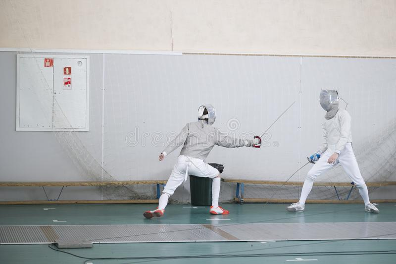 Two teenager fencers practicing their fighting with swords stock photos