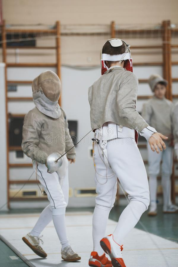 Two teenager fencers with swords on the fencing competition stock image