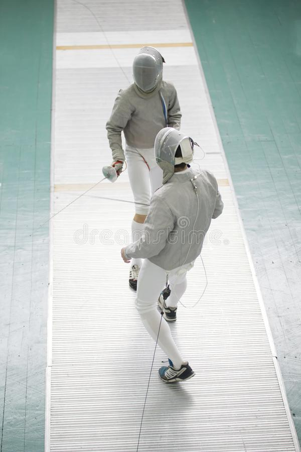 Two teenager fencers with swords on the fencing competition stock images