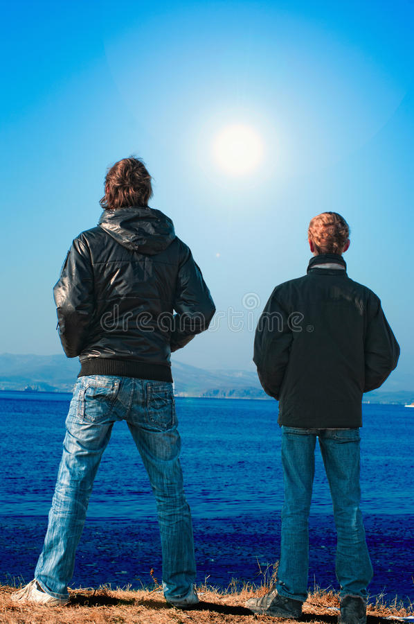 Two teenagers. On an ocean coast looking afar stock photos